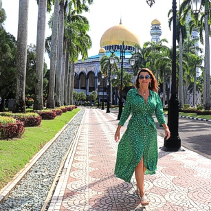 Elegant traveler woman walking in Brunei with a fancy green dress