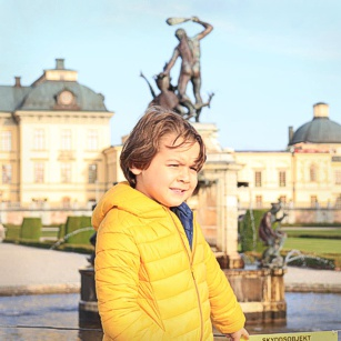 A young boy in front of a Palace near Stockhol in sweden, by Omnimundi