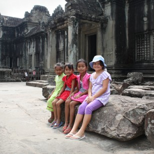 Tourist child sitting among Cambodian girls
