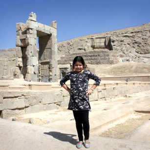 Tourist girl poses near the ruins of Persepolis in Iran under a blue sky, by Omnimundi