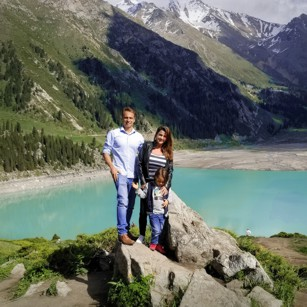 Omnimundi Family standing over a rock in front of Almaty Lake in Kazakhstan