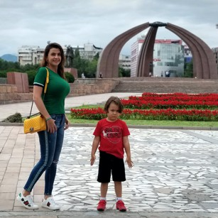 Travelling family posing in a Square in central Bishkek, Kyrgyzstan
