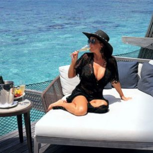 Luxury travel to the Maldives represented here by an elegant woman in swimsuit sitting in a fancy hotel deck