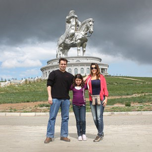 Omnimundi Family of three in Mongolia fields with Ginggis Khaan monument in background