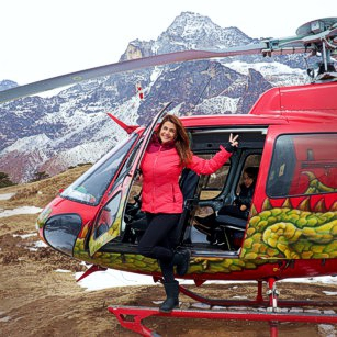 A woman outside of her rental helicopter makes a luxury travel to the slopes of Mount Everest