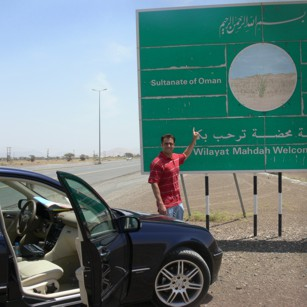 A tourist driving a luxury car in the Oman desert in front of a road sign