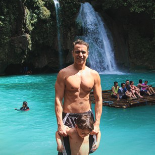 Father and son in swimsuits standing in Kawasan Falls in Philippines during a travel