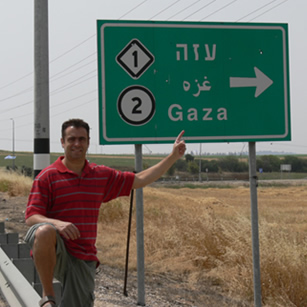 A tourist in front of a road sign in Palestine