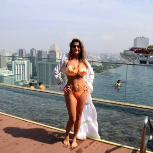 Beautiful fit woman in yellow bikini standing on the rooftop of the luxury Marina Bay Sands hotel in Singapore