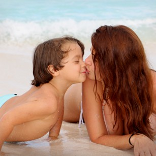 Young boy kissing his mother on a beach in Turks and Caicos by omnimundi