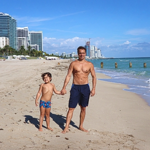 Father and young son standing in Miami Beach in front of the St Regis luxury hotel