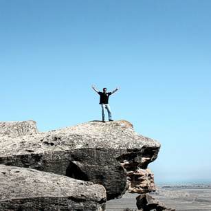 Man stanting on a rock with blue saky in Gobustan, Azerbaijan