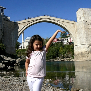 Omnimundi young girl standing under the famous Mostar Bridge in Bosnia
