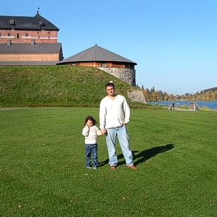 Father and son from Omnimundi family posing near an old castle in Hameenlinna Finland