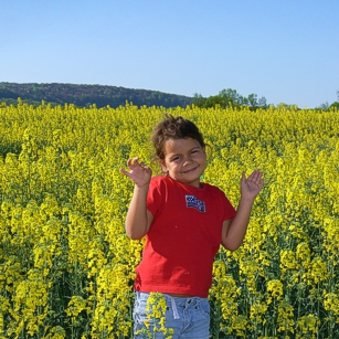 A yellow flower field in Louxembourg with a cute girl
