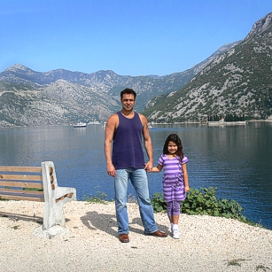 Father and daughter from Omnimundi Family standing at the border of a Fjord in Montenegro