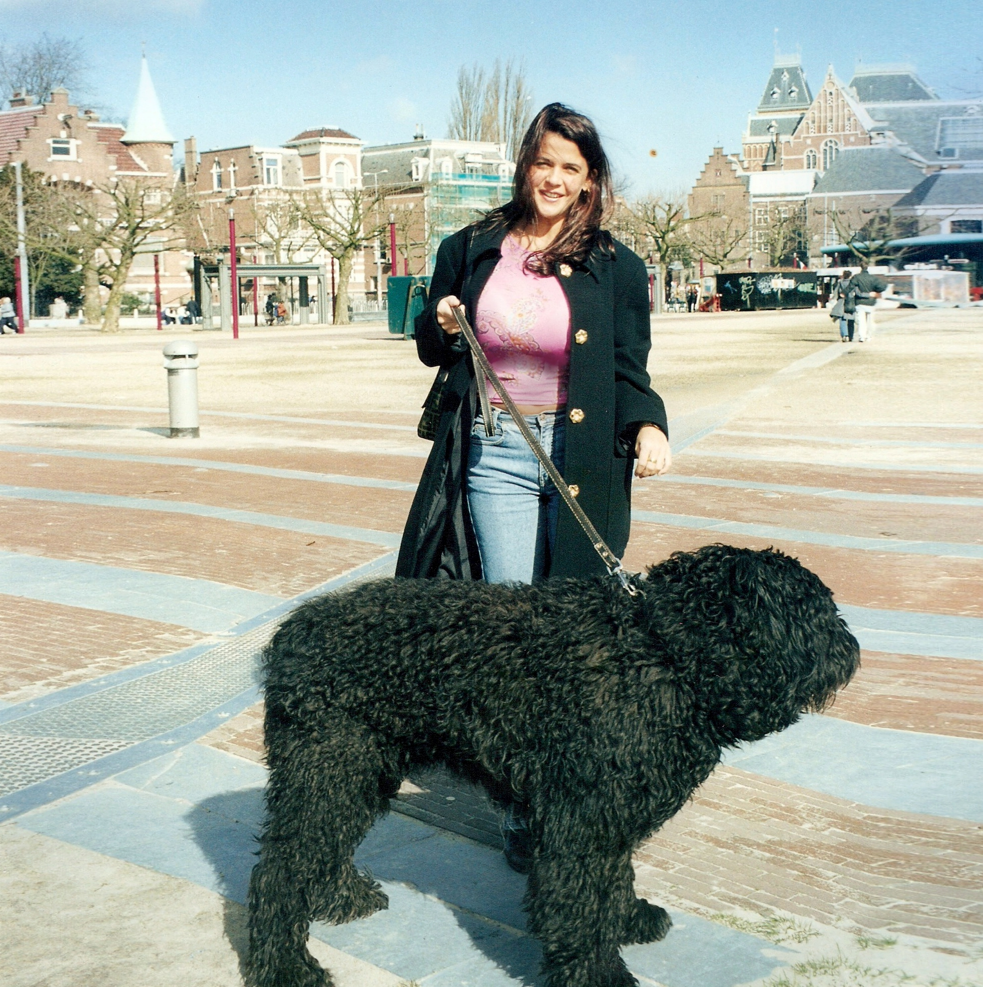 Downtown Amsterdam and a woman holding a big black cute dog