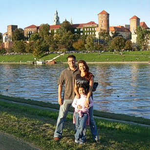 Omnimundi family seen at a border of a river with a castle in Krakow, Poland