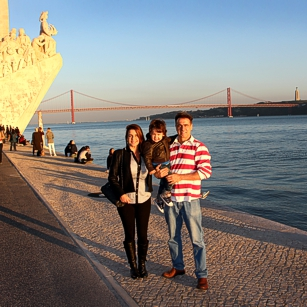 Family of three tourists along the Tejo River in Portugal, by Omnimundi