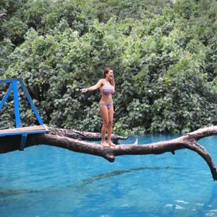 A woman in bikini walking on a rod over a beautiful blue lagoon in Vanuatu, by Omnimundi