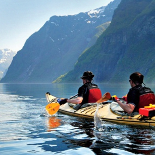 Two adventure sportis in a Kayak paddling inside a beautiful lake with mountains in background
