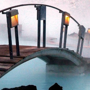 A tiny curved bridge over a blue lagoon in Iceland
